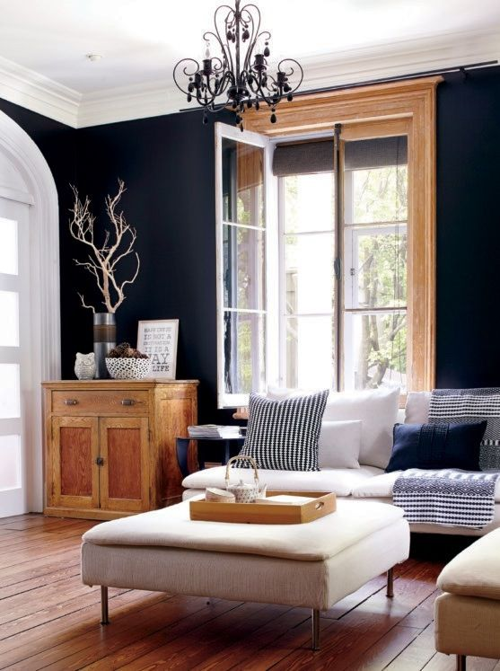 Navy wall, dark wood floor, light/warm accent wood (the paneling), light natural furniture.