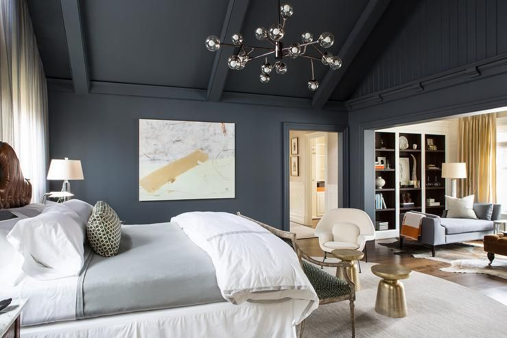 Dark gray bedroom features a vaulted ceiling and a modular chandelier  illuminating a brown leather tufted