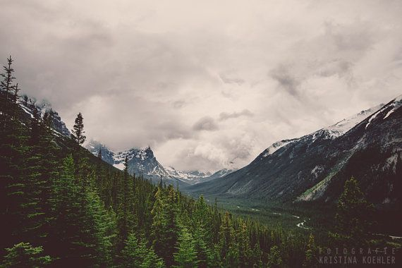 RIDGE: The clouds are drawing lower, swirling around the snowcapped tops and intensifying the colors of the impenetrable forested mountain sides.