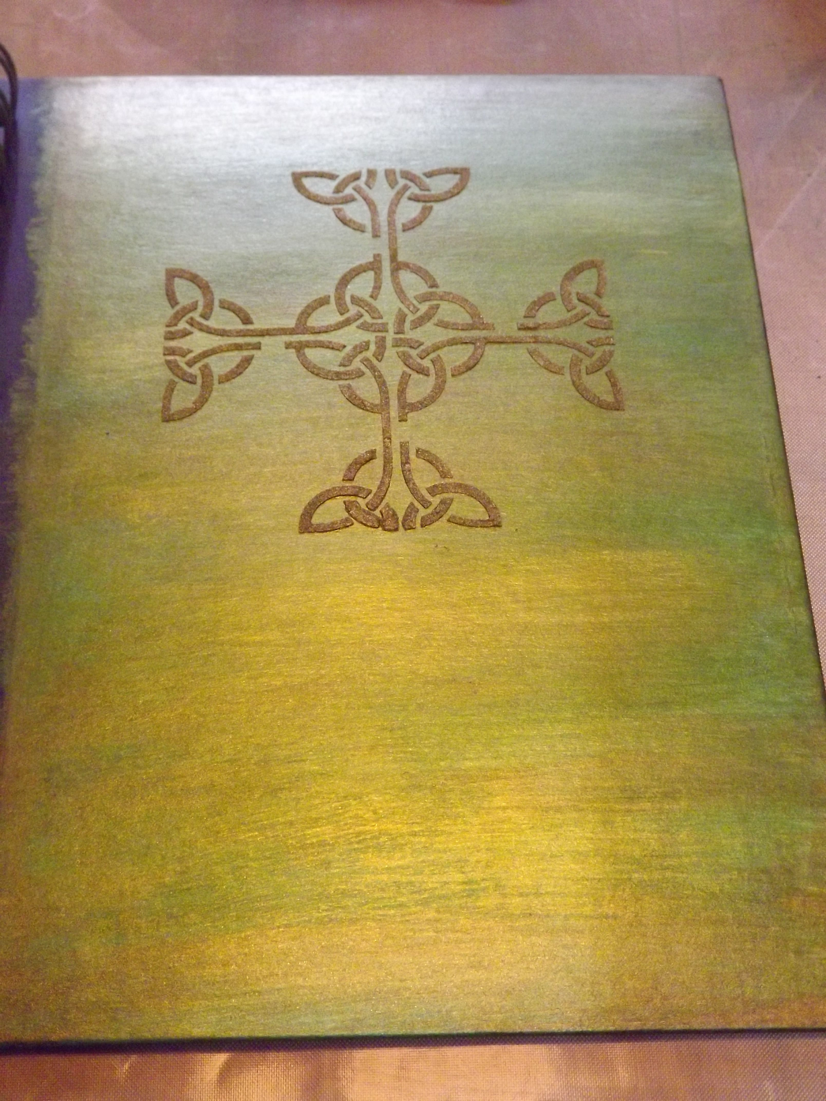 Celtic journal. Cover painted with silks acrylic glazes in 5 shades of green, 1 gold, and 1 brown. Celtic cross made with a delta stencil  and amber gold Ferro special effects paste. Journal cover was finished with a gold and green ribbon. This journal was a gift for a friend.