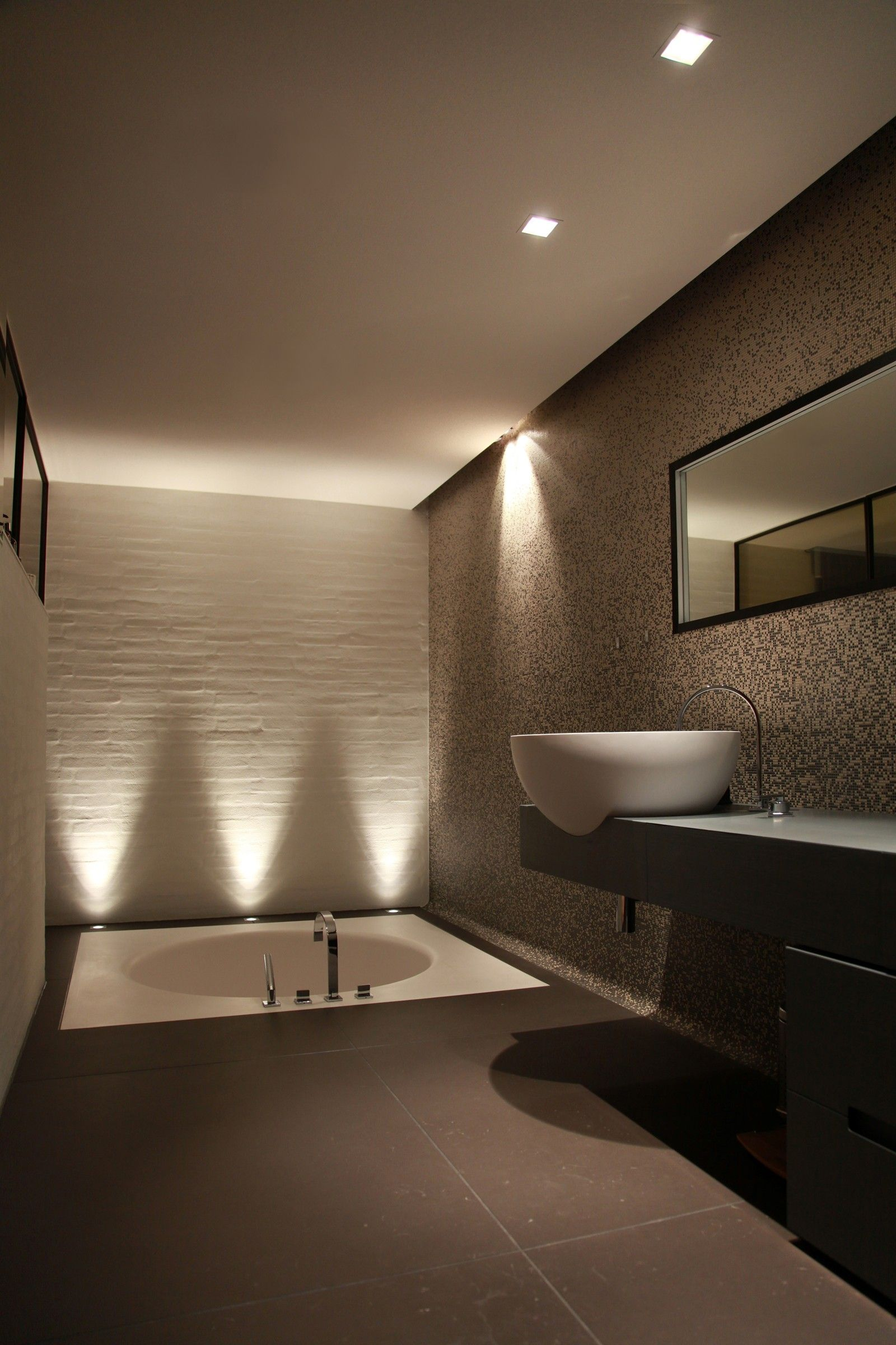 Dramatic up lighting accents sculptural wall tiles