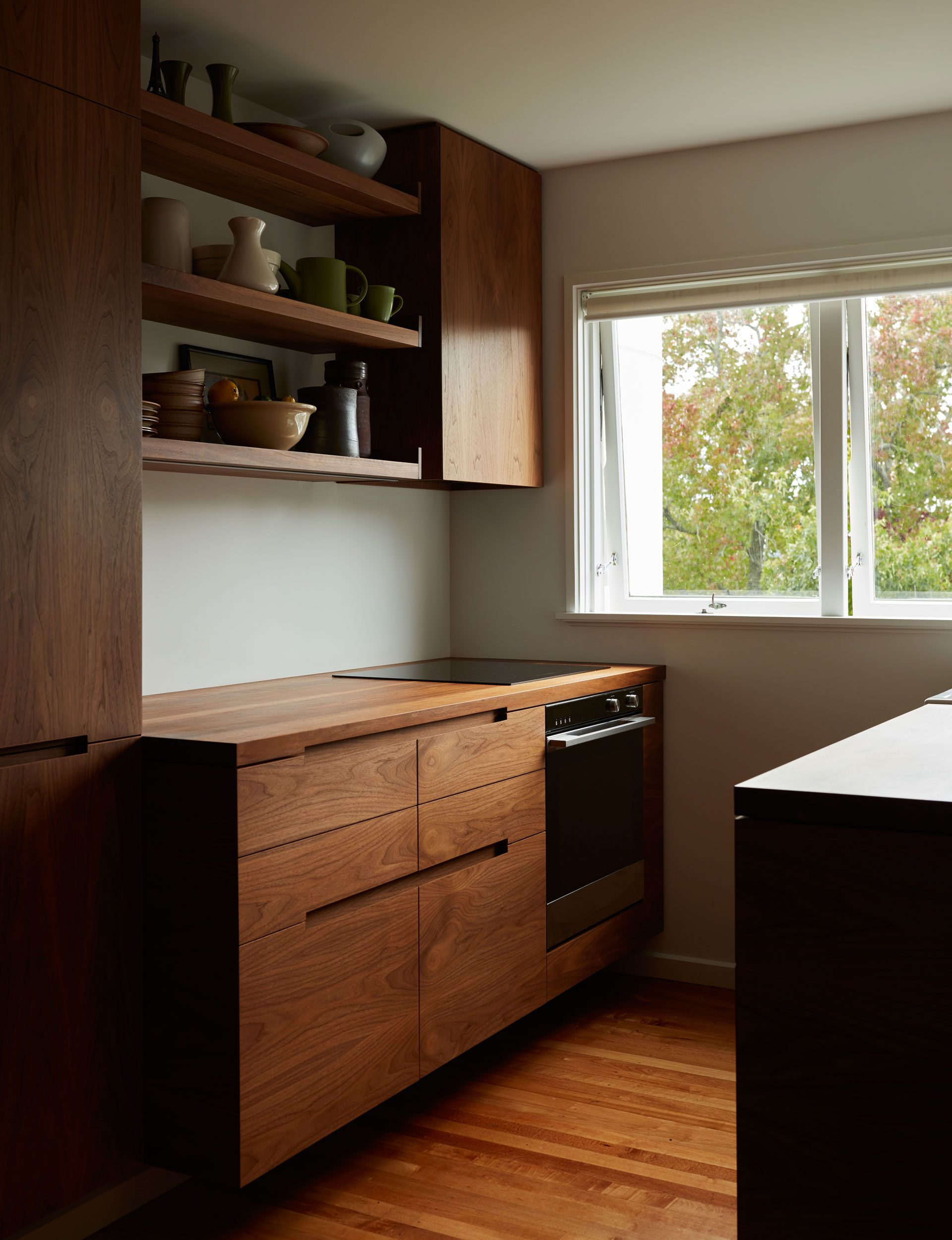 A small apartment kitchen is redesigned with rich walnut cabinetry