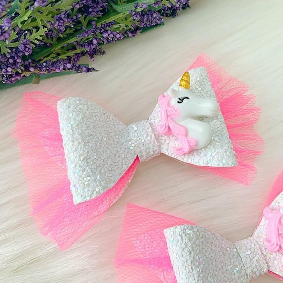 This beautiful Unicorn Bow is made of White Glitter material and Pink Tulle. It is measure around 3 inches. This cute