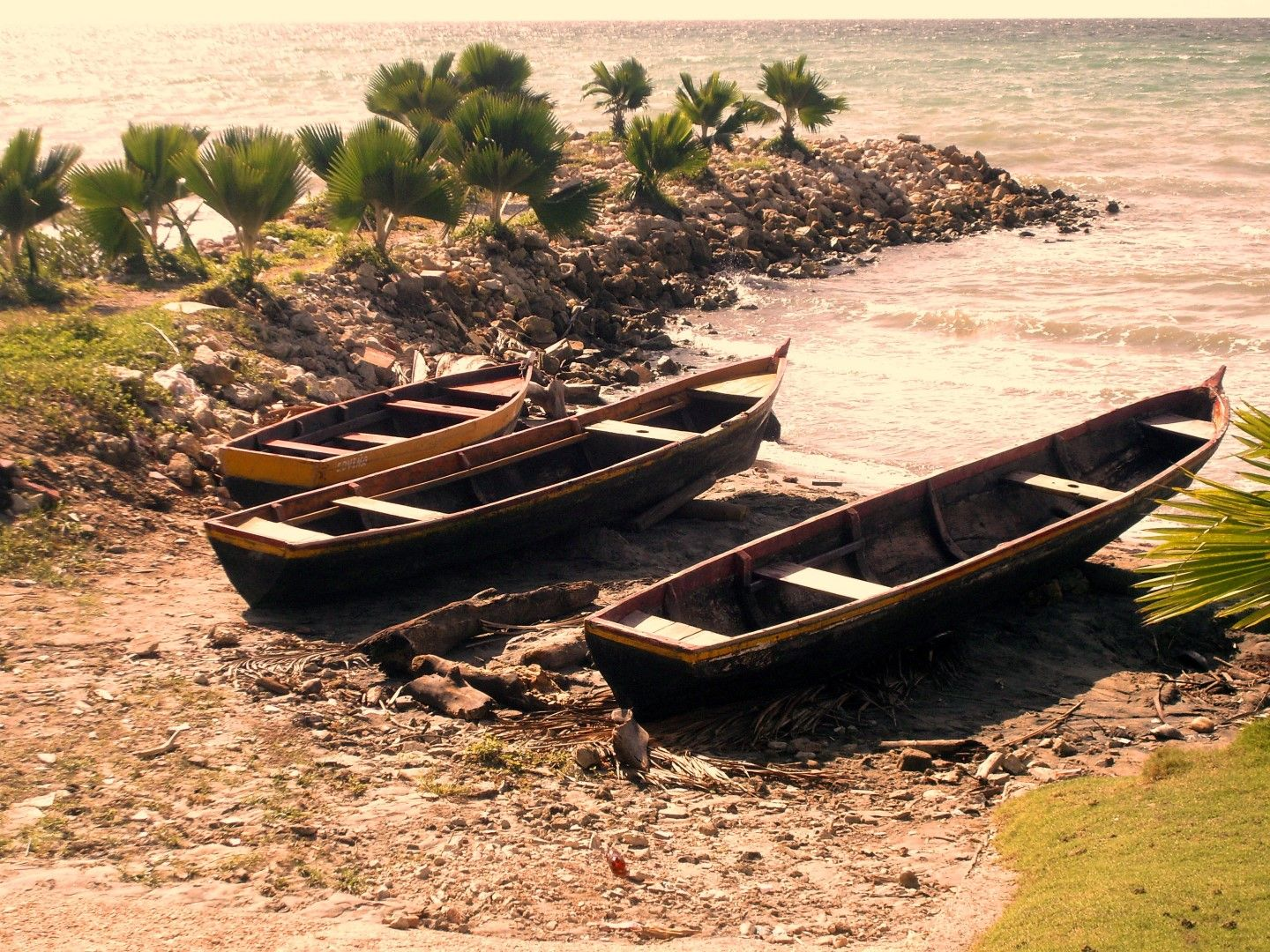 Two canoes laying on the side of the beach of Tolu