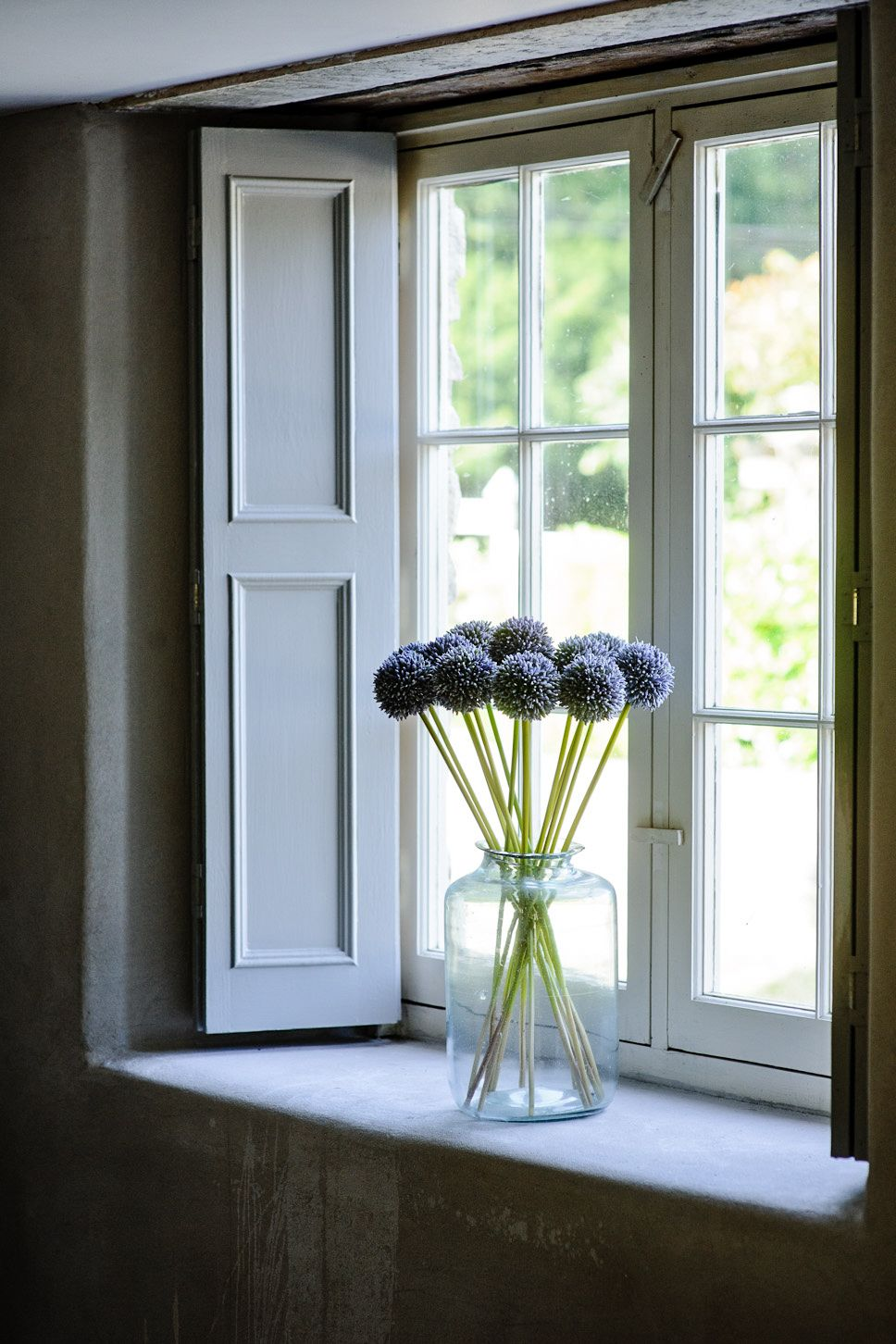 Large Cottage Window With Pale Wooden Shutters.To Top It Of A Clear Large  Vase With Dark Alliums Sits On The Sill.Loove!