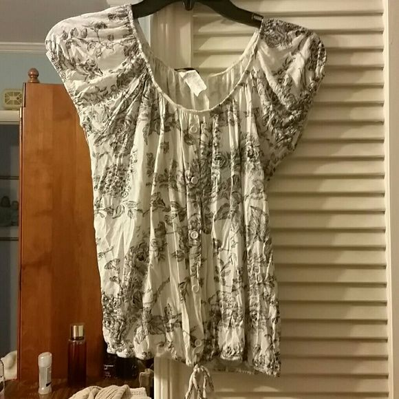 Cute floral top Off white top with floral print. Short sleeves elastic band around hips, beck, and end of sleeves. Tie strings at bottom of front. Decorative buttons up front of shirt. 90% rayon and 10% linen. 21 inches long. agenda Tops Blouses
