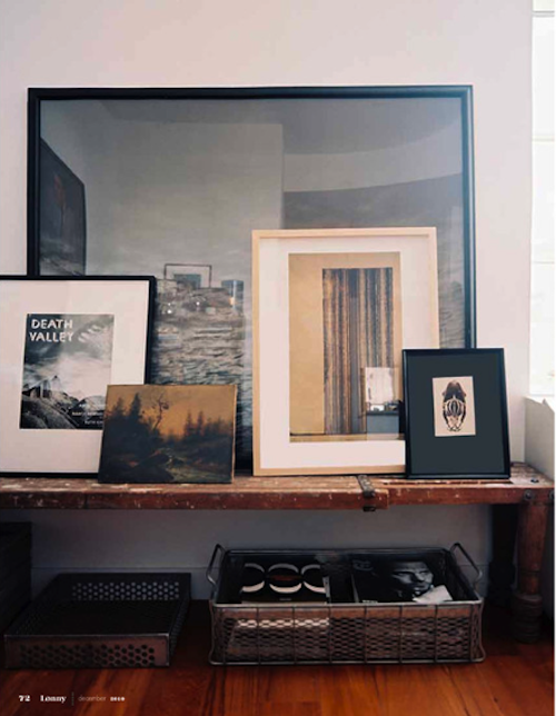 frames layered on top of wood bench with books in steel baskets