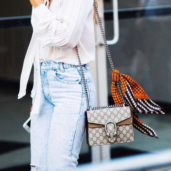 Elevate your accessories by tying a silk scarf over the strap of your bag.