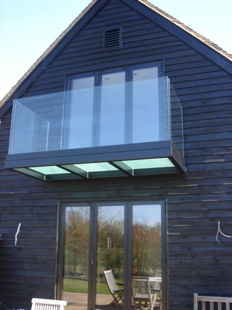 Black powder coated balcony with frosted triple glazed floor and frameless glass balustrade
