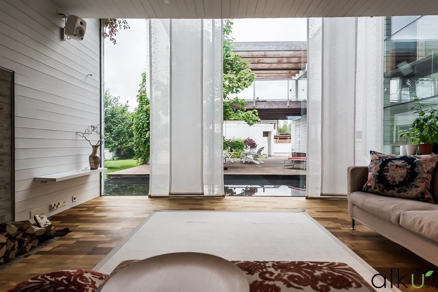 Olohuoneen ikkunasta näkyy todellinen taideteos; vesiallas ja näyttävä terassialue.