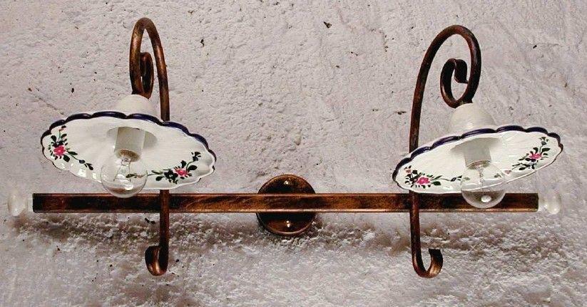 A lampada da parete in metallo e piatti in ceramica decorata