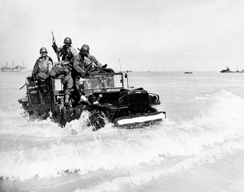 U.S. soldiers ride through the surf at a Normandy beachhead enroute to the inland battlefields, during the Allied invasion of France, June 21, 1944. (AP Photo)