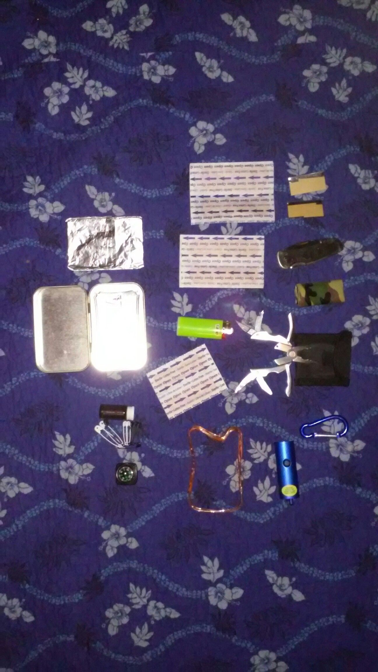 Partial contents of altoids survival kit I made for my dad before wrapping it in camo 550.