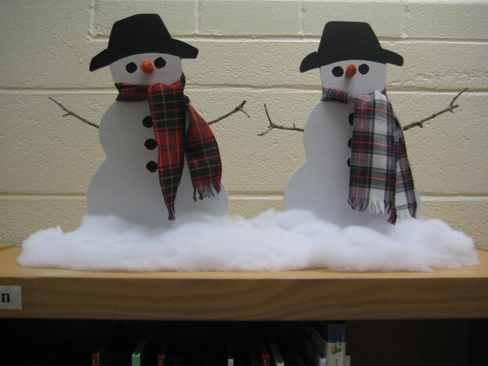 Snowmen cut from plywood, sitting in slot in 1 x 3.  Look better when surrounded by quilt batting snow. On display in library during winter (Dec. & Jan.).