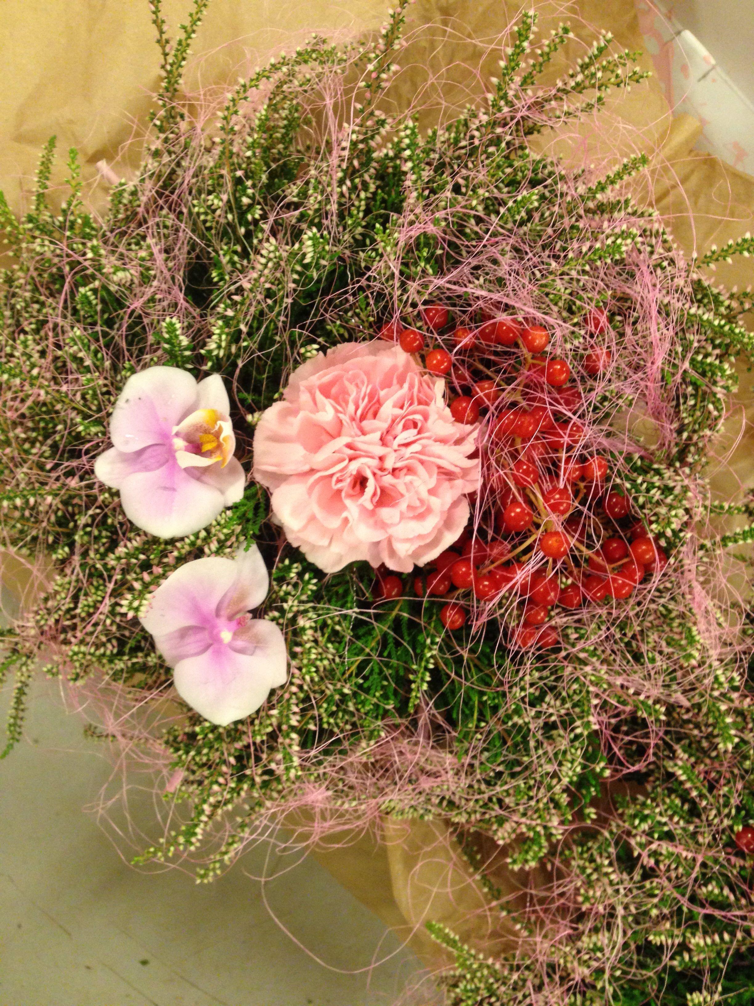 Oppi lyngblomstene stikkes en nellik, 2 orkideer og bunter av bær. Rundt legges et tynt lag av rosa ull.