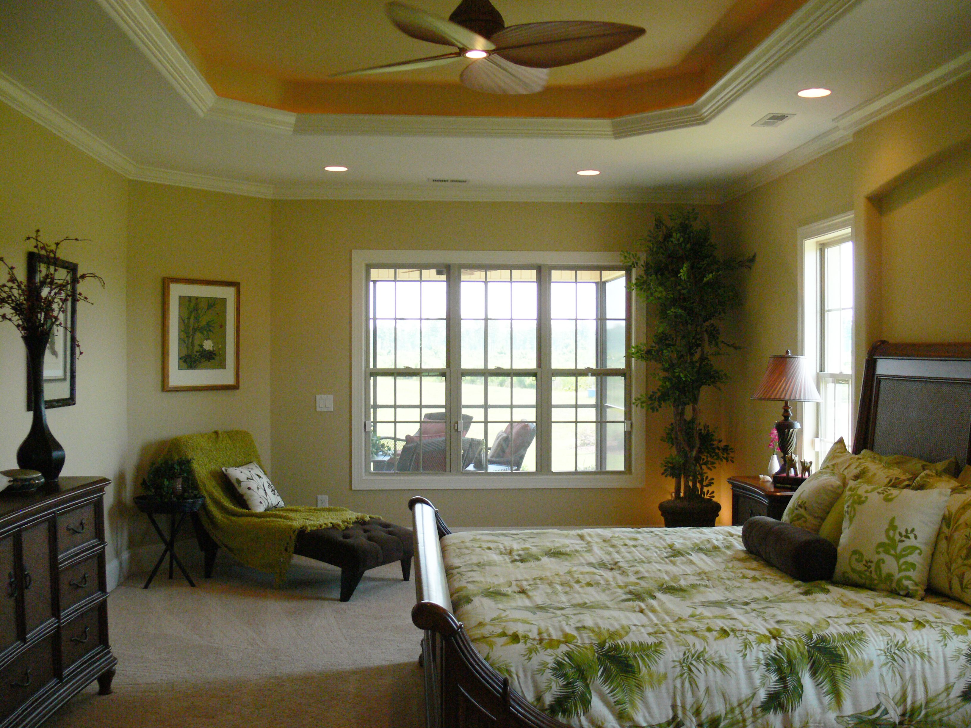 Decorative fan, recessed lighting, tray ceiling, lots of space in this Belize model Logan Home master bedroom.