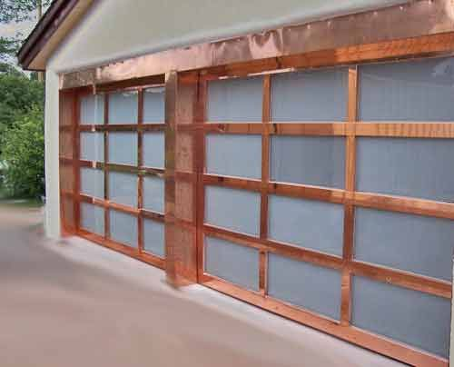 copper garage door with glass laminate panels and copper frame