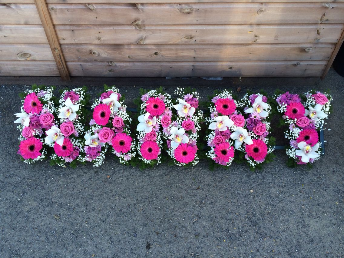 A Contemporary Styled Tribute Spelling Out Nanny Using Pink Gerbera