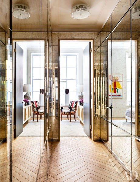 Antiqued mercury glass sheaths a hallway fitted with H. Theophile door hardware | archdigest.com