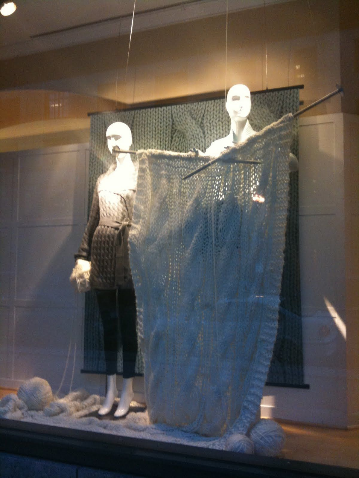 Talbots window display with two mannequins winding a skein by hand. October 2011.
