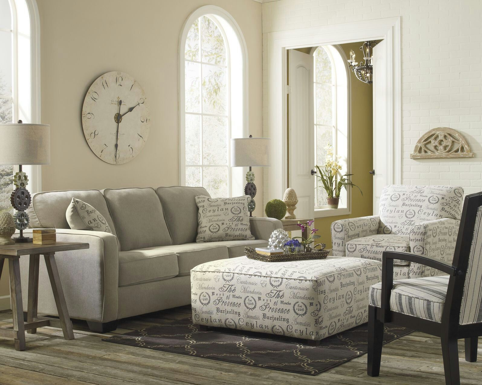 ottoman for living room%0A OTTOMAN COFFEE TABLE Light toned living room stands over grey hardwood  flooring  with neutral grey sofa next to textpatterned white armchair and  matching
