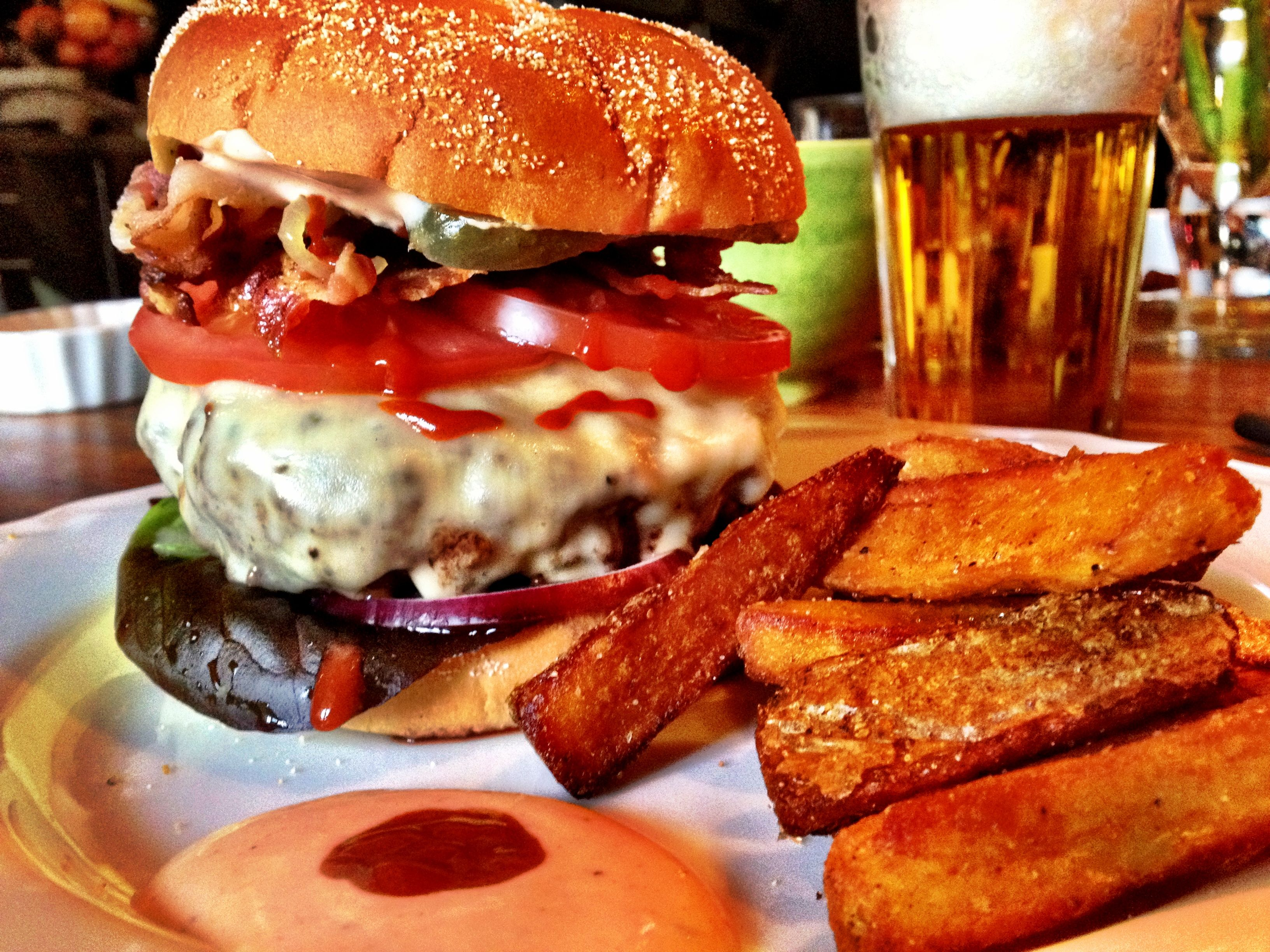 1/4 Kilogram Beef Burger with Fried Onion, Bacon, Melted Cheese, Sriracha Mayo, completed with Large Potato Wedges and a Cold Zlatopramen.