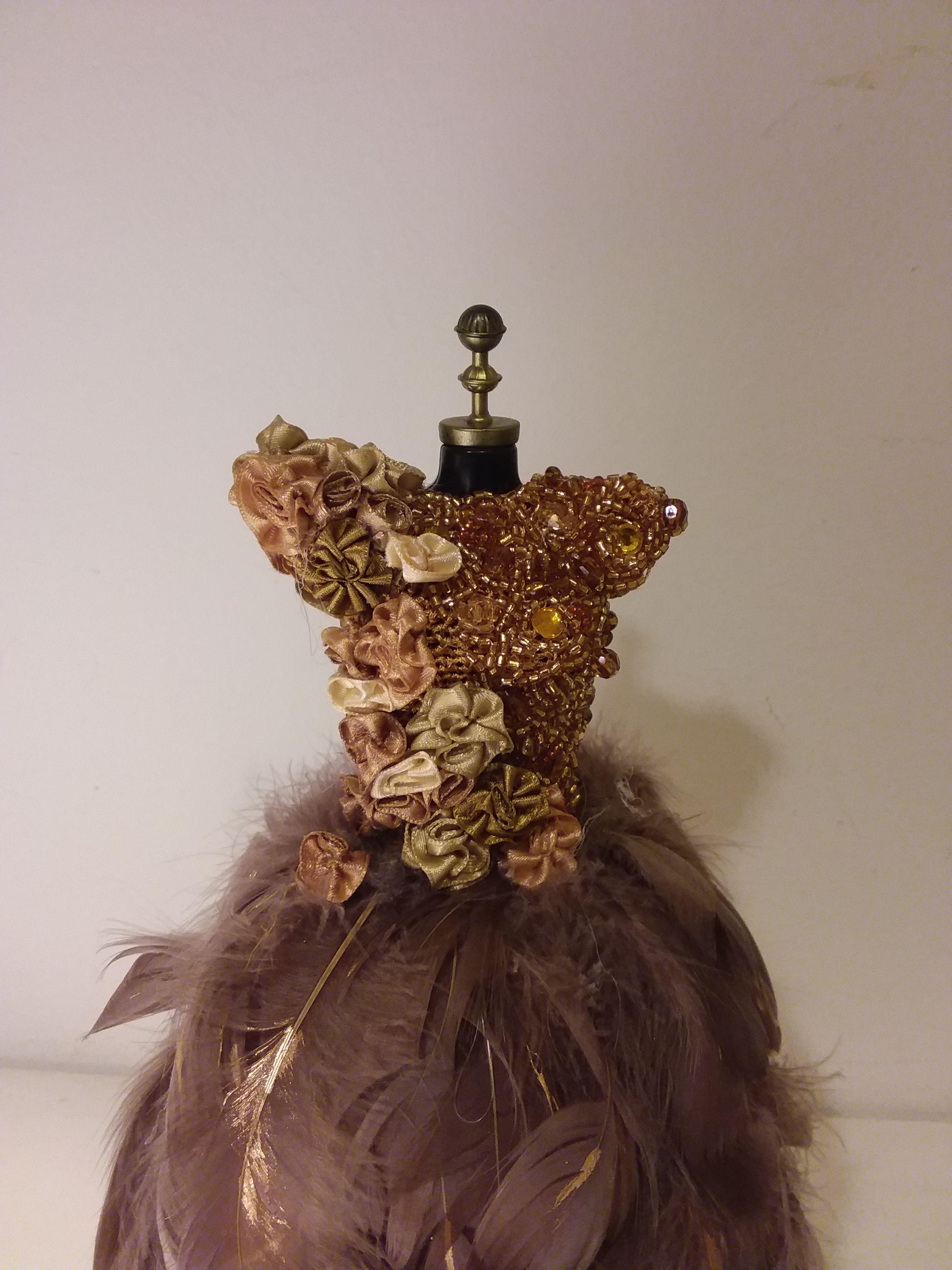 Cuerpo de cristales y flores de raso con falda de plumas con pinceladas en oro