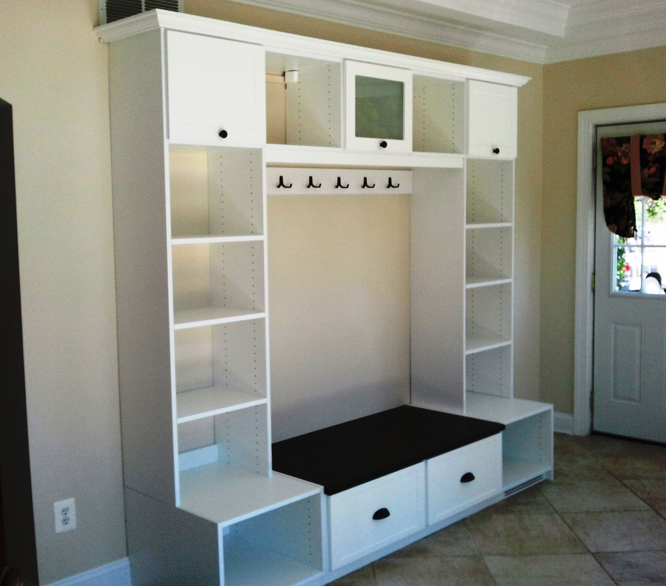 Foyer Closet For Garments : Entryway unit featuring crown molding hooks cubbies