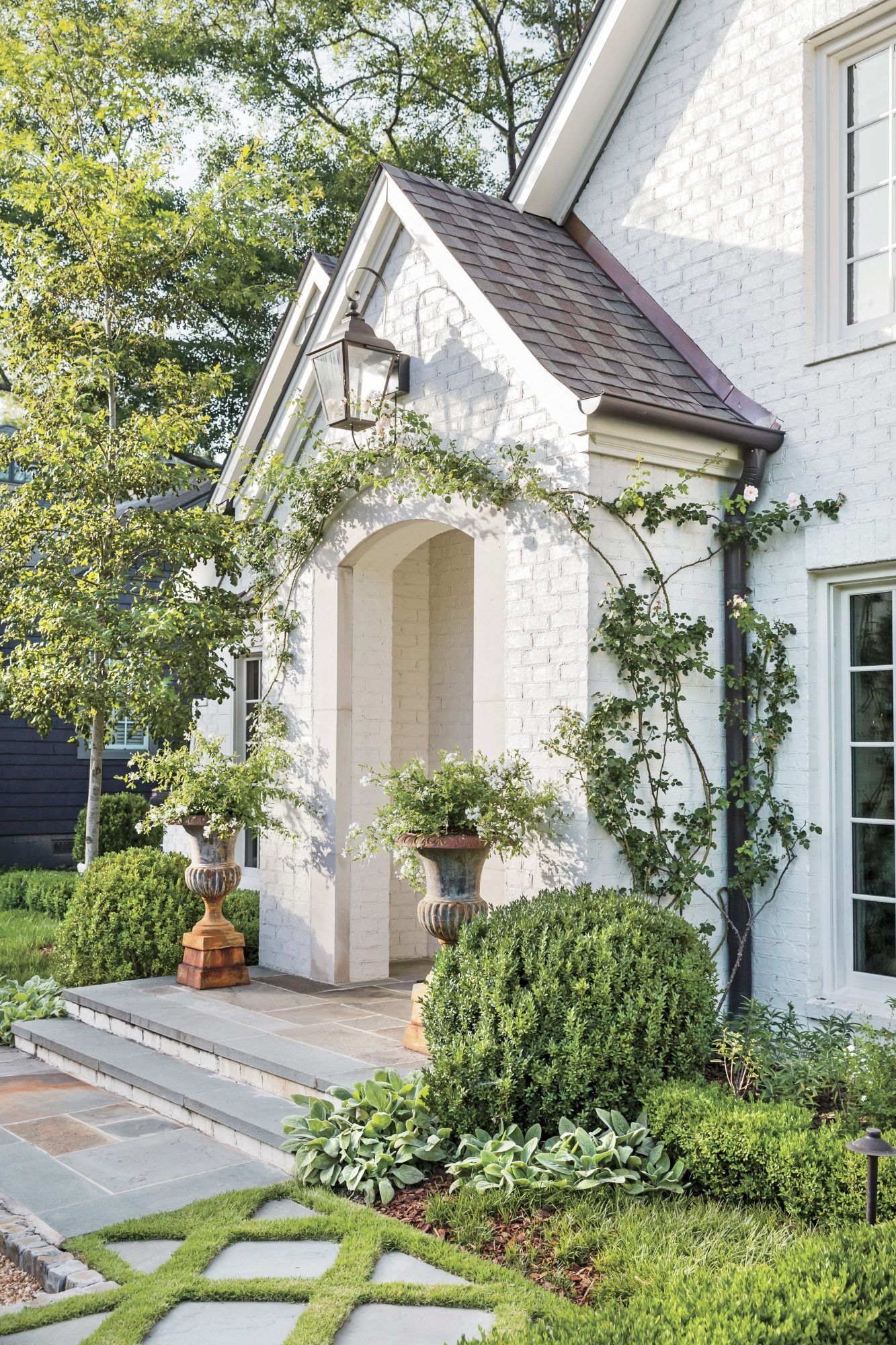 How Landscaping Added Instant Charm to this New Birmingham Home is part of White brick houses, Brick porch, House exterior, Exterior, Curb appeal landscape, White brick - Shapely hedges, bold pathways, colorful plantings, oh my