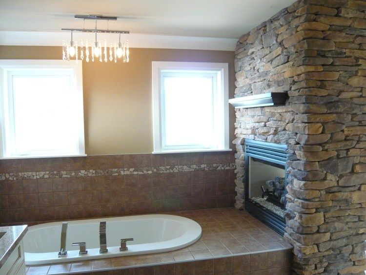 Ensuite Fireplace Soaker Tub Stone Chandelier Tile