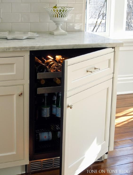 Kitchen Features Creamy White Cabinets Fitted With A White Paneled Beverage Fridge With Pull Out