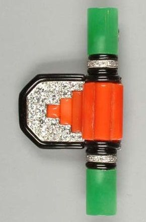 An Art Deco coral, jade and diamond brooch, circa 1930. Set to the centre with three coral batons, between curved bands of black onyx and single-cut diamond-set spacers with jade terminals, suspending a shaped rectangular plaque with pavé-set old brilliant-cut ground, centred by further stepped coral batons, to a black enamel border. #ArtDeco #brooch