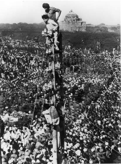 Margaret Bourke-White |  Mourners climb a telephone pole to observe Gandhi's funeral procession in January 1948.