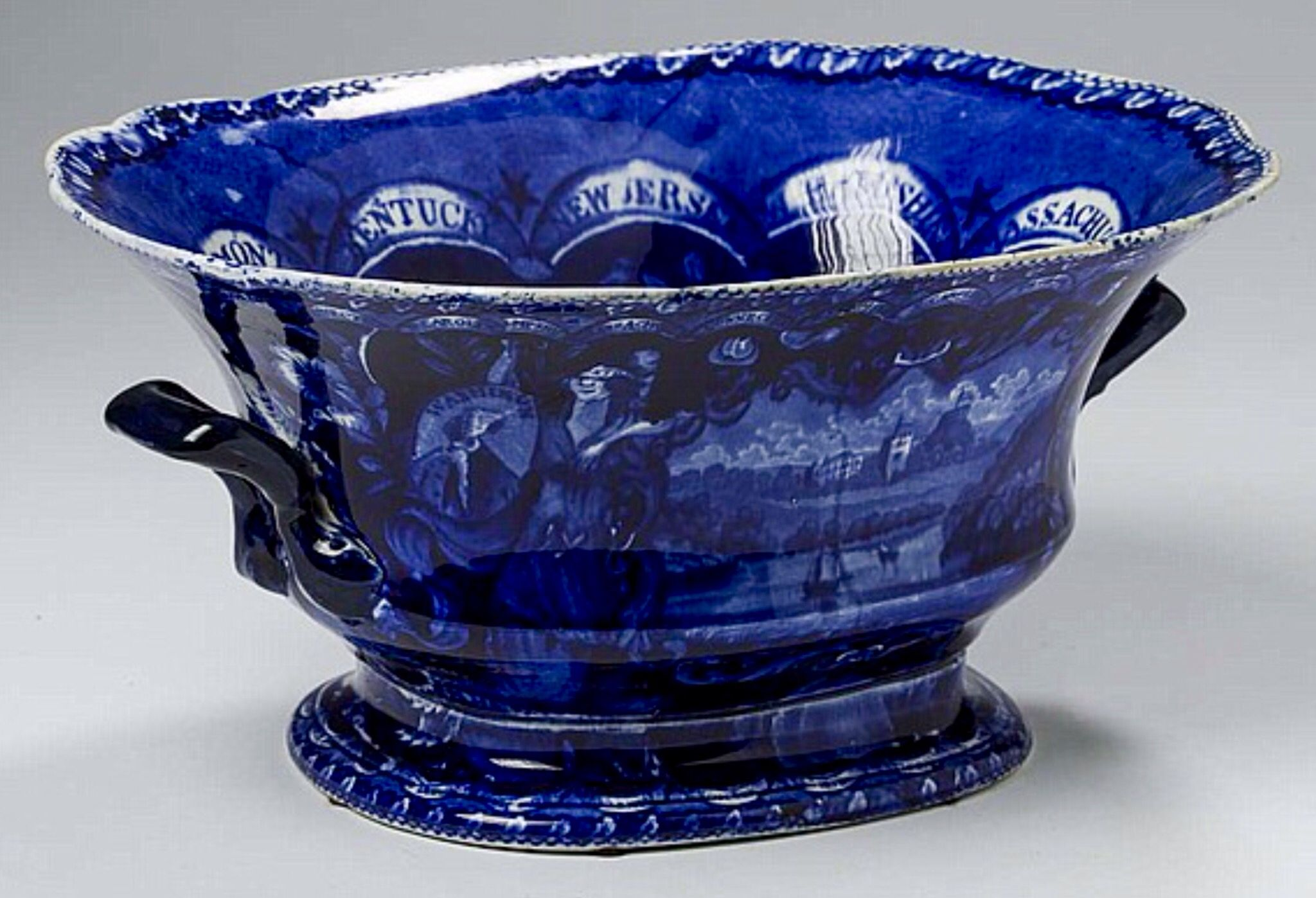 "Northeast Auctions - THE COLLECTION OF CHESTER CREUTZBURG AND DAVID MARTIN - PART ONE. 3/5/16. Lot 60: STATES, AMERICA AND INDEPENDENCE SERIES: MANSION, SMALL BOAT FLYING A FLAG IN FOREGROUND,' STAFFORDSHIRE DARK BLUE TRANSFER-PRINTED FOOTED COMPOTE, JAMES & RALPH CLEWS, COBRIDGE, 1819-36. Estimated Price: $1,200 - $1,800. Realized: $2,280 (1,900). Description: Early impressed crowned ""CLEWS WARRANTED STAFFORDSHIRE"" factory mark. Length 10 3/4 inches. Provenance: William & Teresa Kurau…"