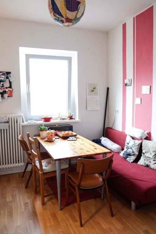Essbereich mit Holztisch, Holzdielen, rot tapezierter Wand