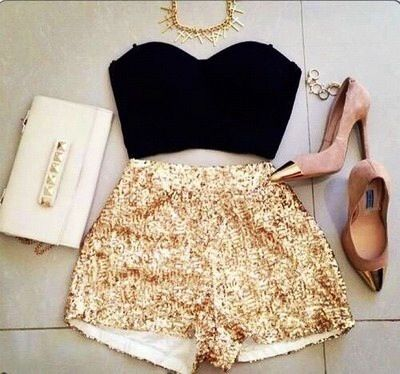 Cute outfit. Gold sparkle shorts, black crop top, clutch, and heels.