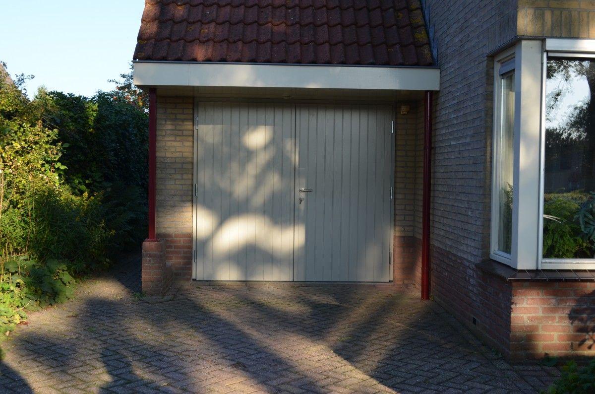 """Openslaande houten garagedeuren model """"Emmen"""" Deurdikte 80mm Dark Red Meranti Links of rechts openslaand (van buiten gezien) Deuren symmetrisch of 1/3-2/3 verdeling Deuren zijn voorzien van een zeer hoogwaardige isolatiekern Rubber tochtkader in zowel de deuren als het kozijn gefreesd Deuren voorzien van een vertikaal """"plankmotief"""" Ons model Mander is een soortgelijk model maar 68 …"""