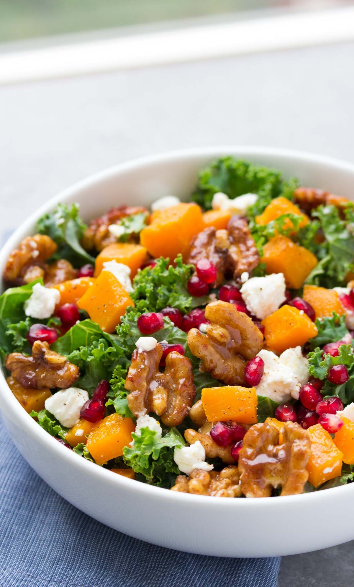 A healthy and festive holiday salad for Thanksgiving, Christmas or any day! This Butternut Squash and Pomegranate Kale Salad with Spiced Honey Walnuts has a yummy maple dressing!