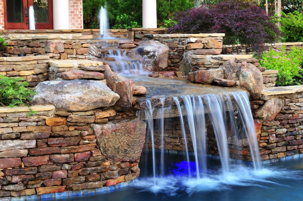 This pool 39 s stacked stone waterfall and fountains provide for Terry pool design jewelry