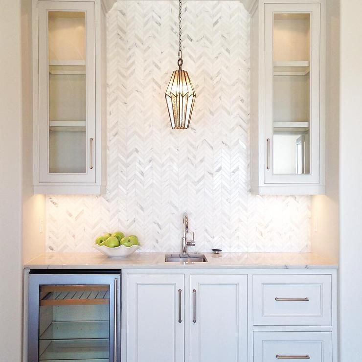 Gorgeous white wet bar boasts white inset cabinets fitted