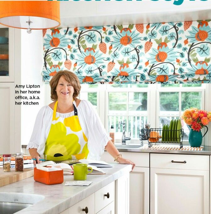 HGTV Amy Lipton's Kitchen. Get the Look with  Peaceful Perch rayon blend fabric at Joann.com.  Apron by Plenl Unikko at Marimekko.com. GSI 64 oz.Enamel Pitcher at peak62.com with flowers by sink.
