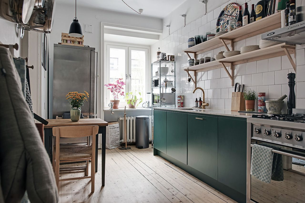 Kitchen with bluegreen cabinets and open shelves