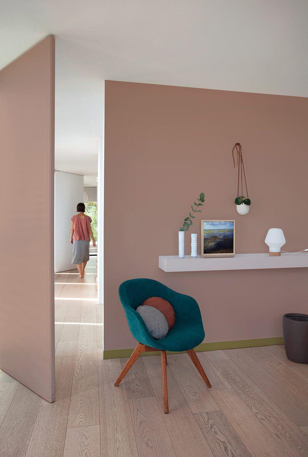 Une chambre bureau peinte en rose poudré avec un fauteuil bleu ...