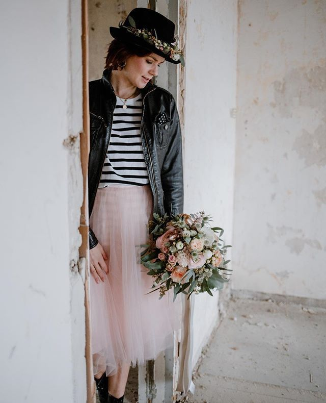 Moderne Braut mit kurzem Brautkleid und Lederjacke für ...