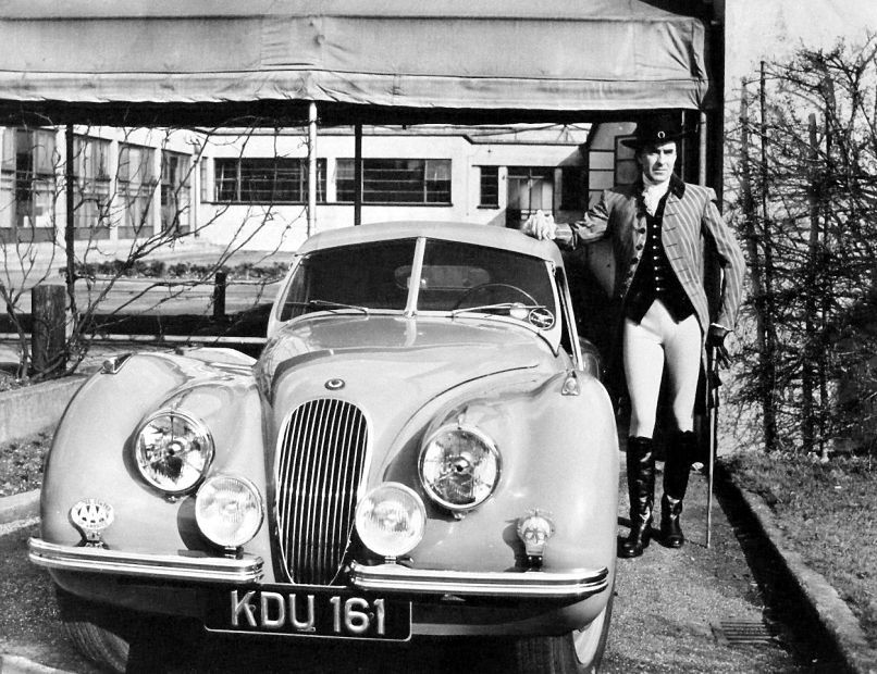 Tyrone Power poses with the Jaguar he acquired while on location in England for The House in the Square