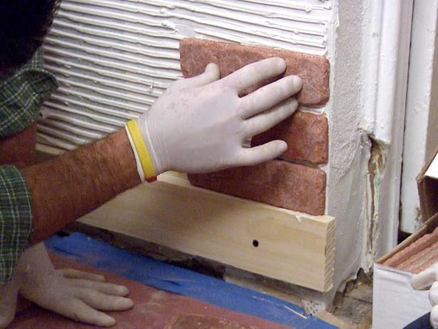 La adición de revestimiento de ladrillos de la pared en este proyecto en el hogar, mientras que el espaciamiento de las filas para agregar la lechada.