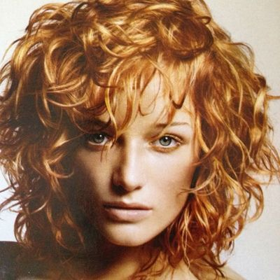medium length shagged out curly hairstyle  without the