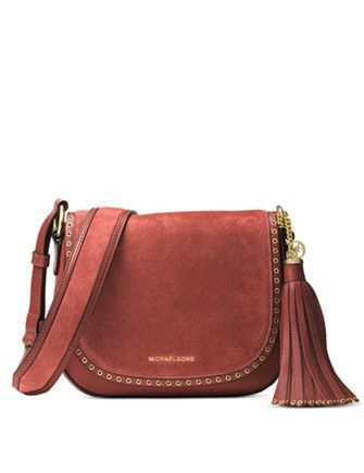 0d31a3b8ca48 Punctuated with petite grommets and hung from a comfortable strap,  of-the-moment saddle bag is cast in sumptuous suede with a swishy tassel  for an ...