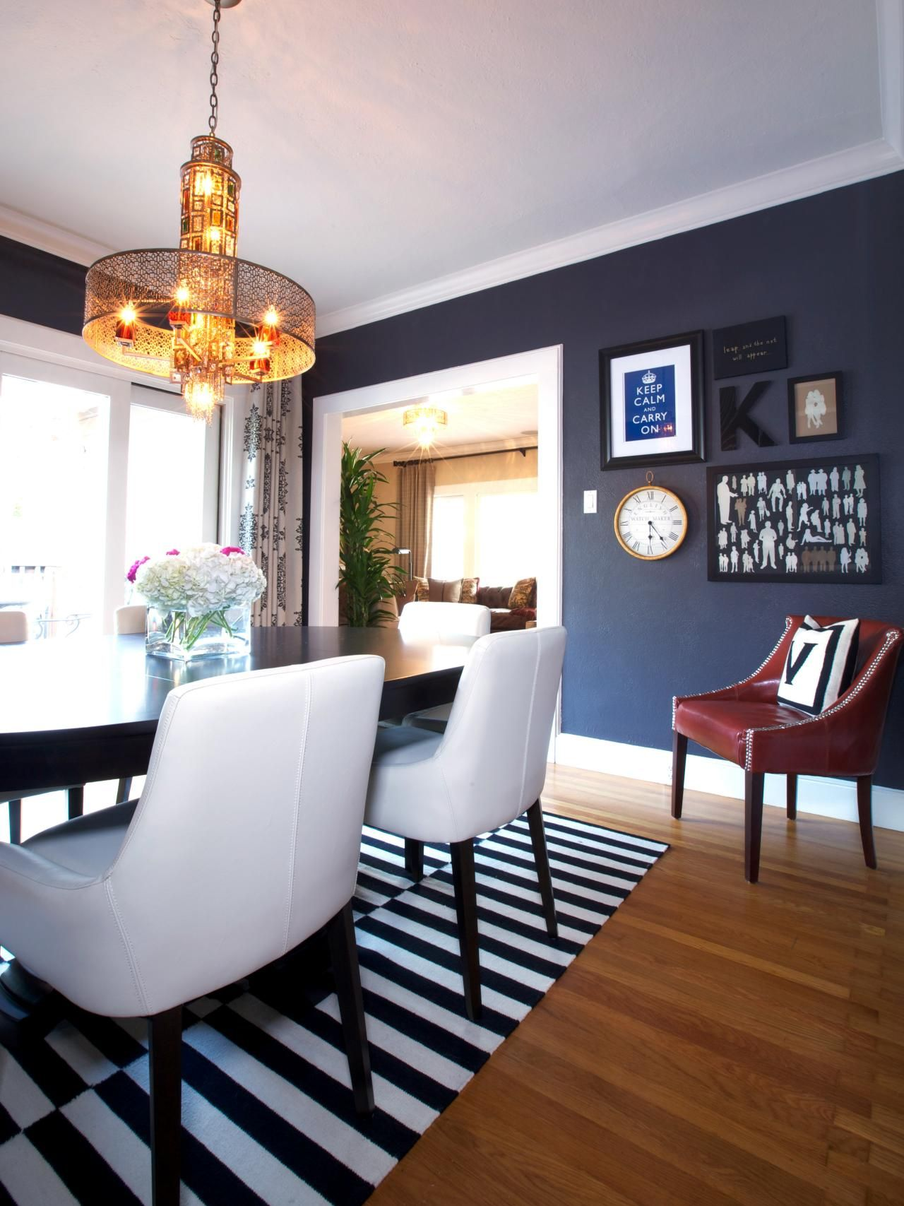 A Dining Room With Blue Suede Walls Features A Black And White Striped Rug,  Red