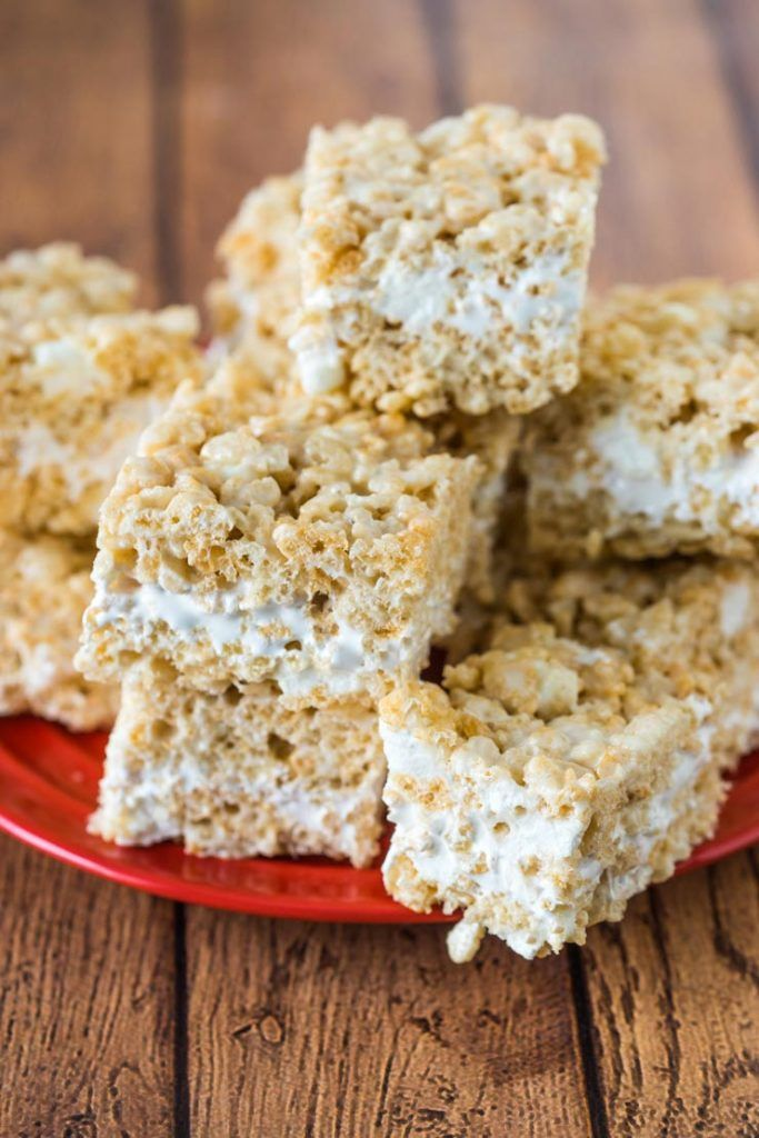 Rice crispy treat recipe with a fluff center on a red plate #crispytreats